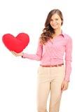 举行一红色心形枕头和微笑的年轻女性 免版税图库摄影