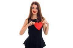 举行一红色心脏和微笑的黑礼服的一个迷人的女孩 免版税库存照片