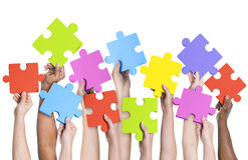 举行七巧板连接概念的人的手 免版税库存照片