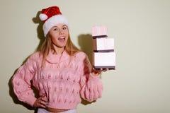 举行三的圣诞老人帽子的美丽的年轻女性 免版税库存图片