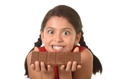 举行与两只在她疯狂的激动的面孔表示前面的手大巧克力块的红色礼服的拉丁孩子 免版税库存照片