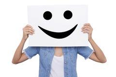 举行与微笑的女孩一张招贴微笑她的面孔前面  图库摄影