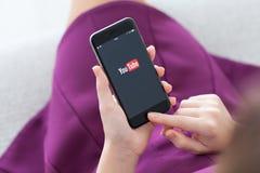 举行与服务YouTube的妇女iPhone 6在屏幕上 免版税库存图片