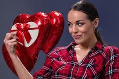 举行与礼物盒心脏庆祝华伦泰` s d的微笑的妇女 免版税图库摄影