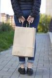 举行与纸袋的女孩生态购物在手上 免版税库存图片