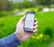 举行与谷歌的男性手iPhone在屏幕上 库存照片