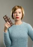 举行与嘴污点的大巧克力块和在糖瘾的妇女有罪面孔表示 免版税图库摄影