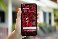 举行与app家的妇女手iPhone x屏幕的 免版税库存照片