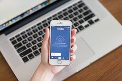 举行与app Tumblr的女性手一白色iPhone 5s在scr 库存照片
