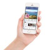 举行与Facebook app的女性手白色苹果计算机iPhone 5s 免版税库存照片