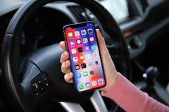 举行与IOS 11的妇女手iPhone x在汽车 免版税库存图片