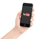举行与YouTube app商标的女性手黑苹果计算机iPhone 5s 库存照片