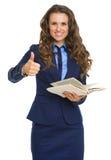 举行书和显示的微笑的女商人赞许 图库摄影