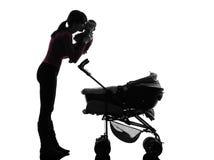 举行亲吻的妇女摇篮车婴孩剪影 免版税库存照片