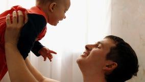 举行他的儿子的手和微笑的一个年轻愉快的父亲的慢动作 影视素材