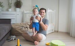 举行他的10个月的愉快的微笑的父亲被定调子的照片小儿子 图库摄影
