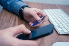举行信用卡和一键入在电话的手做网上购买 库存图片
