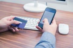 举行信用卡和一键入在电话的手做网上购买 免版税图库摄影
