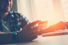 举行信用卡和使用的微笑的人膝上型计算机 拟订dof重点现有量在线浅购物非常 免版税库存照片