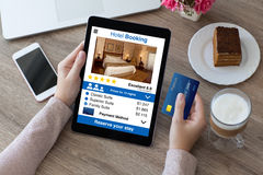 举行信用卡和计算机片剂app旅馆预定的妇女 免版税库存照片