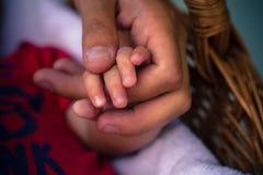 举行儿童的小的手育儿概念的父亲的手 免版税库存图片