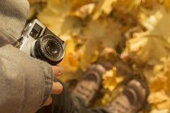 举行减速火箭的照相机和身分在黄色叶子的女性报道了地面 库存图片