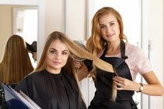 举行剪刀、梳子和h的美丽的白肤金发的女性美发师 库存照片