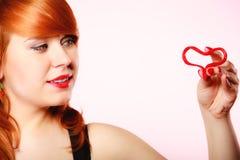 举行华伦泰红色心脏爱标志的女孩 红色上升了 库存图片