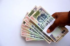 举行印地安货币的人的手 库存图片
