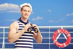 举行双筒望远镜和身分在小船的水手 免版税库存图片