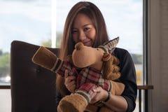 举行和使用与一个逗人喜爱的鹿玩偶的一名美丽的亚裔妇女 免版税图库摄影