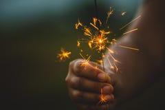 举行和使用与在节日的火闪烁发光物的妇女 免版税库存照片