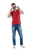 举行和偷看在太阳镜的年轻偶然愉快的人在照相机 免版税图库摄影