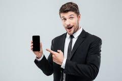 举行和指向在黑屏智能手机的惊奇年轻商人 库存图片