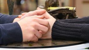 举行和接触每其他的愉快的夫妇手在商城的咖啡馆 抚摸男性手的女性手 影视素材
