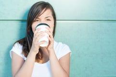 举行咖啡和喝和享用的可爱的女孩 免版税库存图片