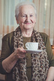 举行咖啡杯和微笑的资深妇女 图库摄影