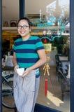 举行咖啡杯微笑的亚裔女服务员 免版税库存图片