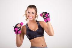 举行哑铃和微笑的愉快的健身妇女 免版税库存图片