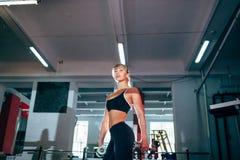 举行哑铃的坚强的健身妇女 免版税库存照片