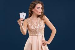 举行啤牌卡片的赢取的组合在深蓝背景的年轻美丽的妇女 一点二 免版税库存照片