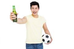 举行啤酒瓶和橄榄球的爱好者 库存图片