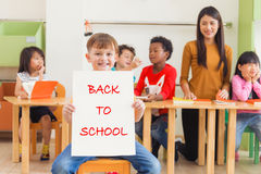 举行回到与愉快的面孔的学校海报的逗人喜爱的男孩在幼儿园教室,幼儿园教育概念 免版税库存照片