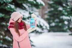 举行圣诞节烛光的美丽的妇女户外在美好的冬天雪天 免版税库存照片