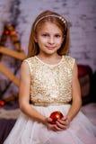 举行圣诞节球和微笑的女孩 免版税库存图片