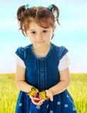 举行在一只大蝴蝶的手上的小女孩 库存图片