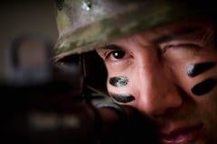 举行在他的英俊的年轻战士画象递准备好一杆的步枪射击,剔出他的眼睛有更多精确度 图库摄影