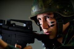 举行在他的英俊的年轻战士画象递准备好一杆的步枪射击,穿军服,绘了他的 免版税库存照片