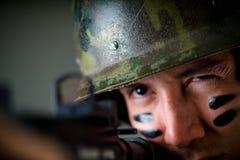 举行在他的英俊的年轻战士画象递准备好一杆的步枪射击,穿军服,绘了他的 库存照片