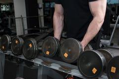 举行在健身房的肌肉爱好健美者人大黑铁哑铃 人用一臂之力干涉解决在健身房 健身房和fitnes 免版税库存图片